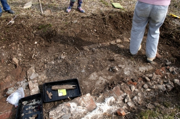 Trench 1A showing un-mortared bricks edging its E side and exterior wall to its W