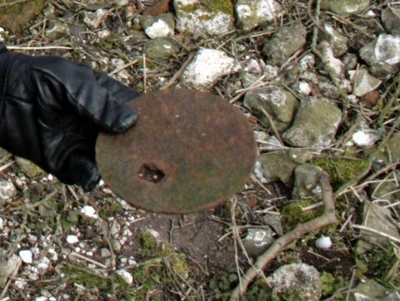 Cast iron lid of stove found on surface of rubble mound