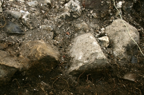 Demolition rubble in vicinity of outside toilet
