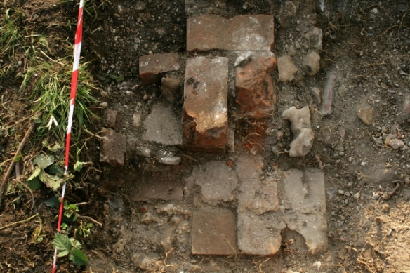 Looking W from door of 'woodshed' at brick quoin of junction with kitchen/scullery