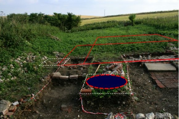 Photo of exvacavtion with wall lines and possible location of a well drawn in