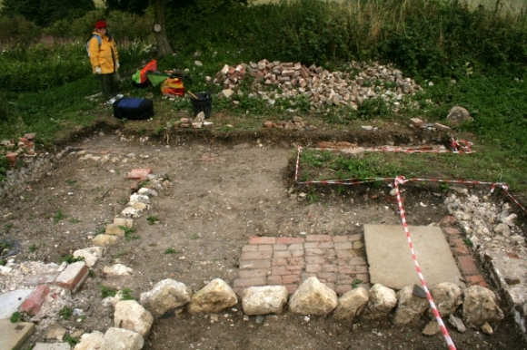 Looking E from garden/farmyard wall across area to front of house, including unexcavated area over possible water tank