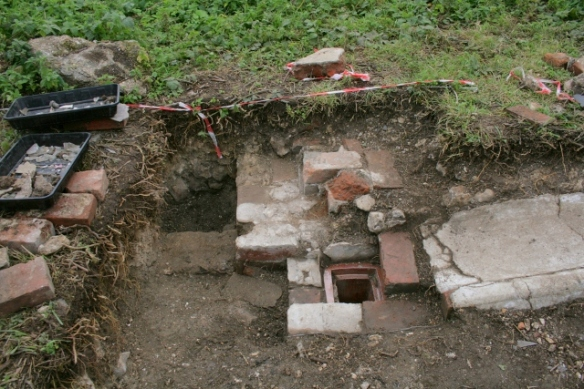 Looking S from 'woodstore' doorway at ceramic drain and concrete gully outside kitchen/washhouse