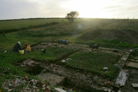 Looking SW from demolition rubble mound at excavation S of cottage