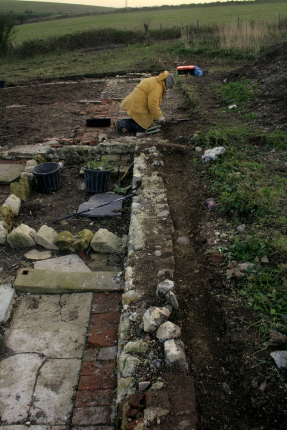 Looking S at boundary wall between cottage/garden and farmyard