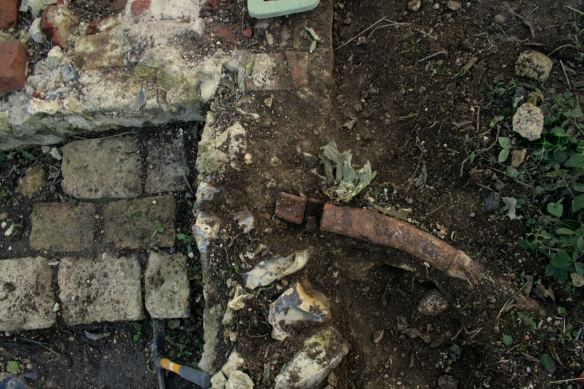 Looking S over water pipe, garden/farmyard wall, stone blocks, and NW corner of cottage walls