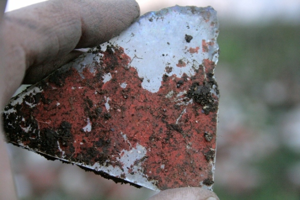 Reverse of mirror showing outer surface of anti-corrosion red-lead paint over reflective silver metal