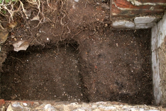 Looking S at gap between bases of 'laundry copper' and chimney