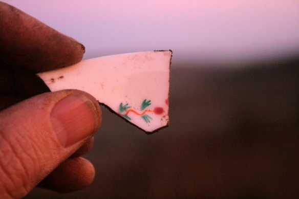 Ceramic shard, in late afternoon sun, from excavation of demolition rubble from E of chimney base