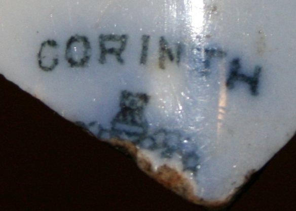 Reverse of blue and white shard bearing 'CORINTH' name over part of a crown design