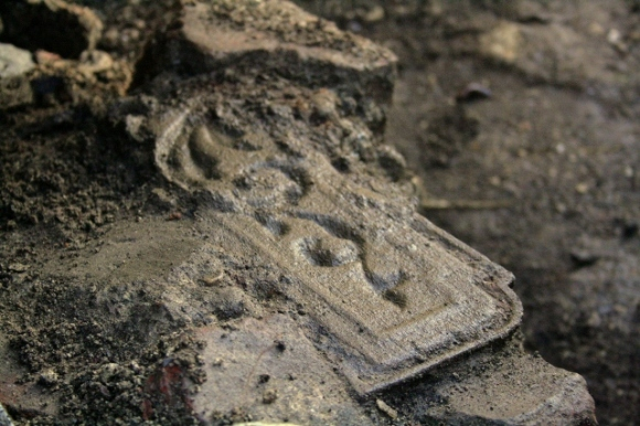 Part of a cast iron fireback embedded in masonry near base of demolition rubble near base of chimney