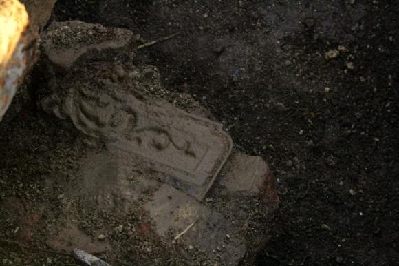 Part of a cast iron fireback embedded in masonry near base of demolition rubble near chimney base