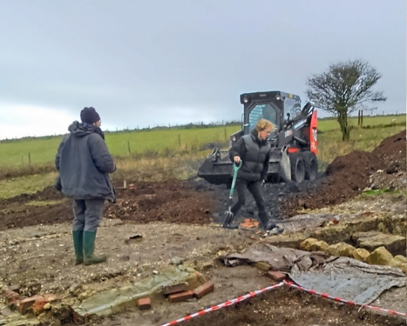 Looking SW at backilling of dig site